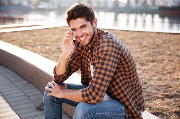 Wesoły młody człowiek w koszuli w kratę siedzi i rozmawia przez telefon komórkowy na zewnątrz