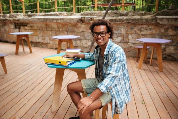 Wesoły młody człowiek w okularach i koszuli w kratę siedzi w kawiarni na świeżym powietrzu