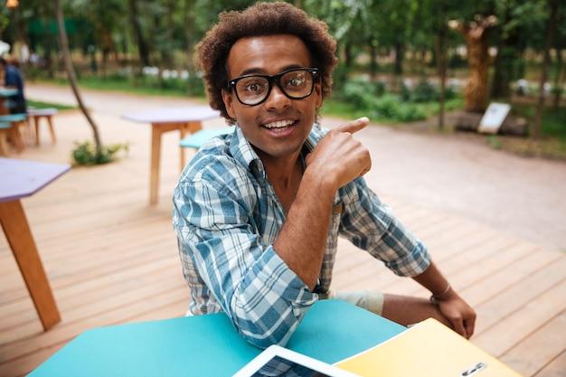 Wesoły młody człowiek w okularach, siedząc w kawiarni i wskazując