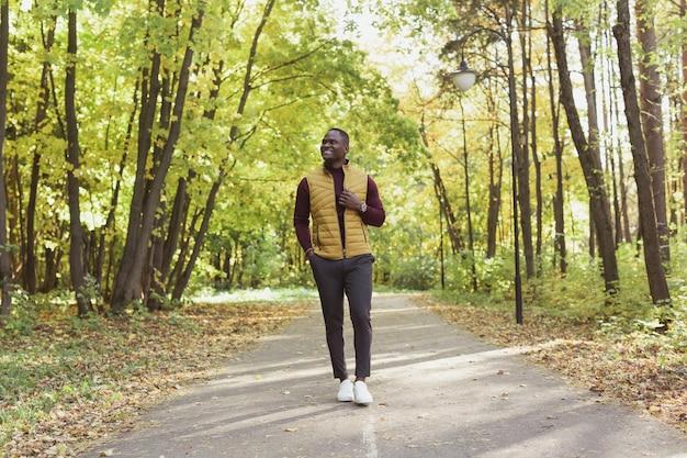 Wesoły młody człowiek w stylowych ubraniach chodzi w jesiennym parku na koncepcji słonecznego ciepłego jesiennego dnia