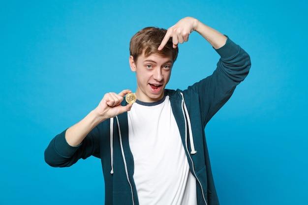 Wesoły młody człowiek w ubranie wskazując palcem wskazującym na przyszłej walucie bitcoin na białym tle na ścianie niebieski. koncepcja życia szczere emocje ludzi.