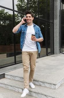 Wesoły młody człowiek w zwykłych ubraniach, pijący kawę na wynos i rozmawiający przez telefon komórkowy, stojąc nad budynkiem