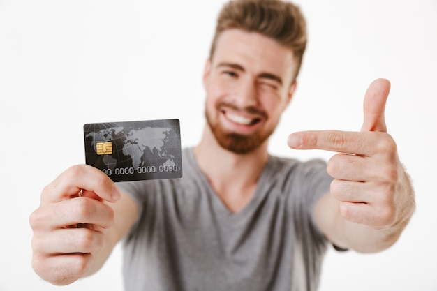 Wesoły młody człowiek wskazując kartą kredytową.