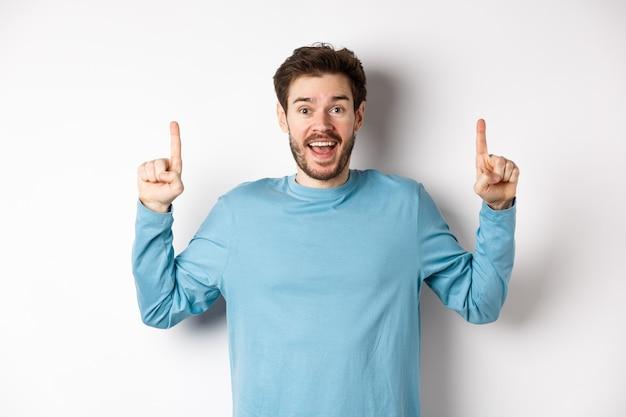 Wesoły młody człowiek wyświetlono reklamę z szczęśliwym uśmiechem, wskazując palcami na niesamowite logo banner, stojąc na białym tle.