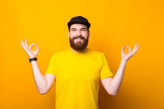 Wesoły młody człowiek z brodą na żółtym robi gest zen i uśmiechnięty, spokojny i relaksujący czas