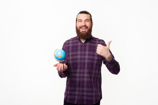 Wesoły młody człowiek z brodą w kraciastej koszuli, trzymając kulę ziemską i pokazując kciuk do góry