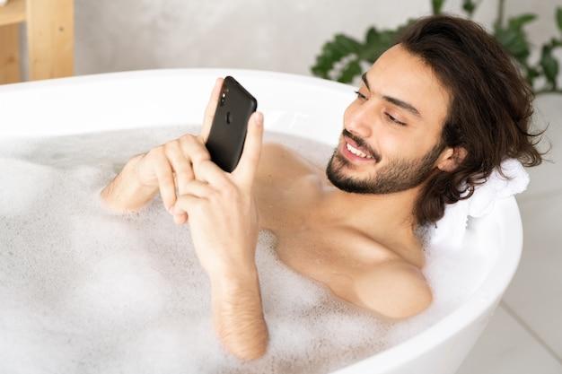 Wesoły młody człowiek ze smartfonem ogląda wideo lub robi selfie, leżąc w wannie wypełnionej wodą i pianą