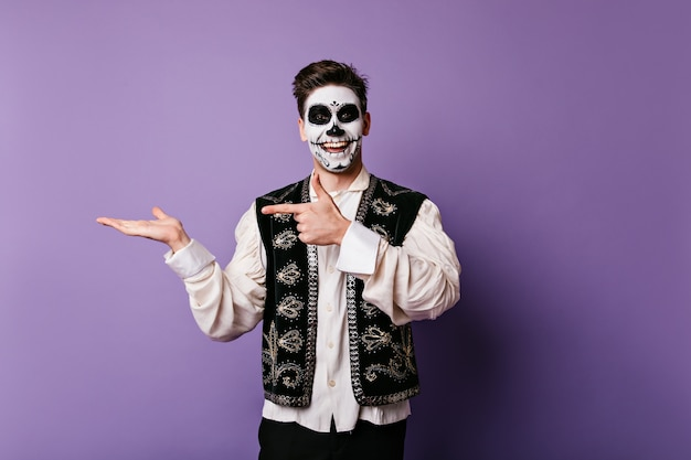Wesoły młody człowiek ze szczerym uśmiechem wskazuje palcem na rękę. kryty migawka faceta z makijażem halloween z miejscem na tekst na odizolowanej ścianie.