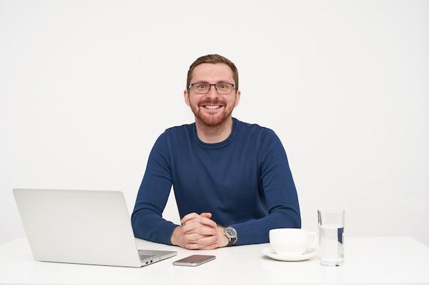 Wesoły młody dość brodaty jasnowłosy mężczyzna w okularach, trzymając złożone ręce na stole, patrząc szczęśliwie na aparat z uroczym uśmiechem, odizolowany na białym tle