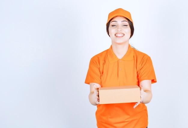 Wesoły młody kurier trzyma pudełko na białej ścianie