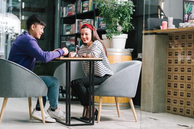 Wesoły młody mężczyzna i kobieta siedzą przy stoliku w kawiarni i patrzą w kamerę na małym statywie