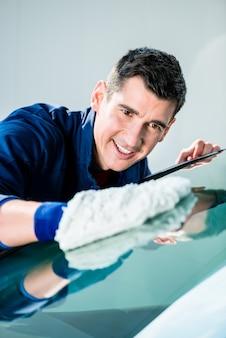 Wesoły młody mężczyzna robotnik do polerowania samochodu z białą miękką rękawicą z mikrofibry w myjni automatycznej