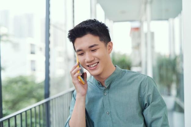 Wesoły młody mężczyzna rozmawia przez telefon na balkonie