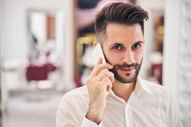 Wesoły młody mężczyzna utrzymujący uśmiech na twarzy podczas rozmowy przez telefon