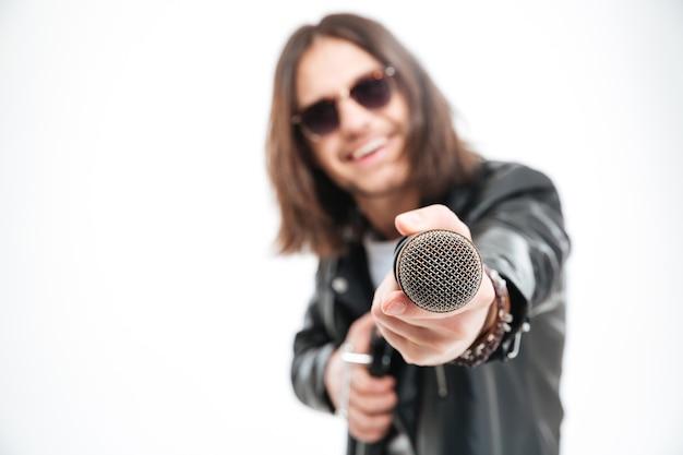 Wesoły młody mężczyzna z długimi włosami w okularach przeciwsłonecznych daje mikrofon i oferuje ci śpiewanie na białym tle