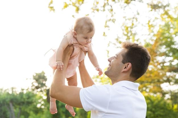 Wesoły młody ojciec bawi się ze swoją małą córeczką