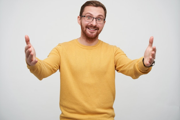 Wesoły młody piękny brunet w okularach z brodą pozuje z szeroko otwartymi ramionami, patrzy pozytywnie i uśmiecha się radośnie