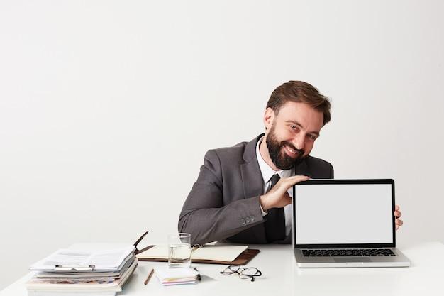 Wesoły młody przystojny brodaty biznesmen z krótkimi brązowymi włosami w szarym garniturze, siedząc przy stole roboczym na białej ścianie, pokazując ekran swojego laptopa i uśmiechając się szeroko