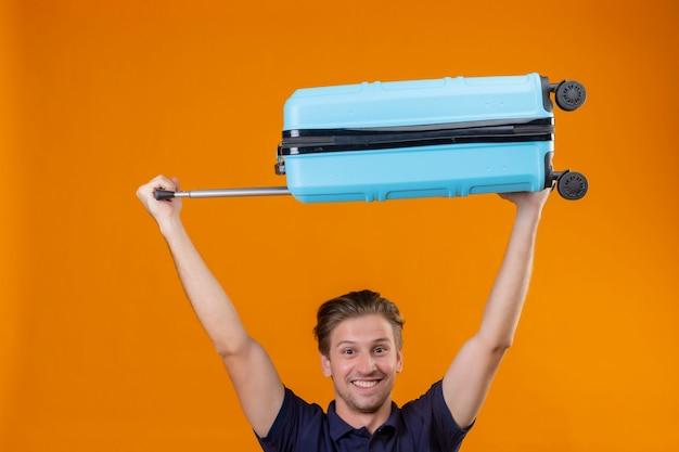 Wesoły młody przystojny podróżnik mężczyzna stojący z walizką nad głową podekscytowany i szczęśliwy na pomarańczowym tle