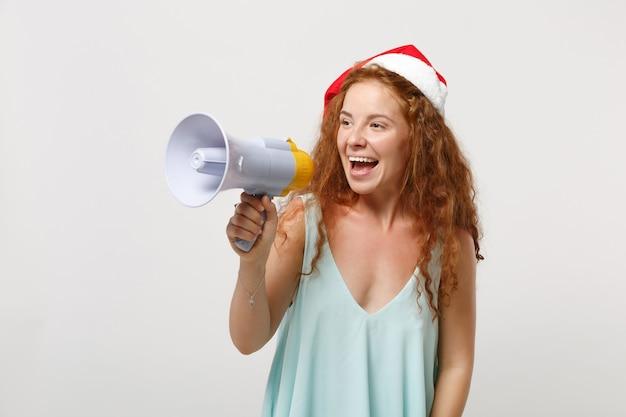 Wesoły młody rudy santa dziewczyna w lekkie ubrania, boże narodzenie kapelusz na białym tle na tle białej ściany w studio. szczęśliwego nowego roku 2020 celebracja wakacje koncepcja. makieta miejsca na kopię. krzyk w megafonie.
