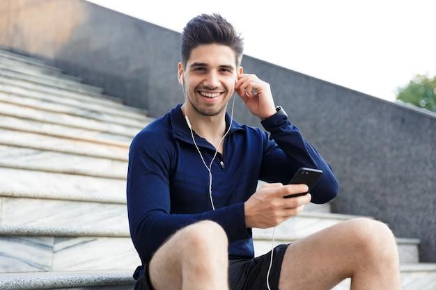 Wesoły młody sportowiec, słuchanie muzyki przez słuchawki, siedząc na zewnątrz