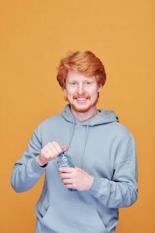 Wesoły młody spragniony mężczyzna z zębatym uśmiechem, otwierając plastikową butelkę wody, stojąc przed kamerą na żółtej ścianie