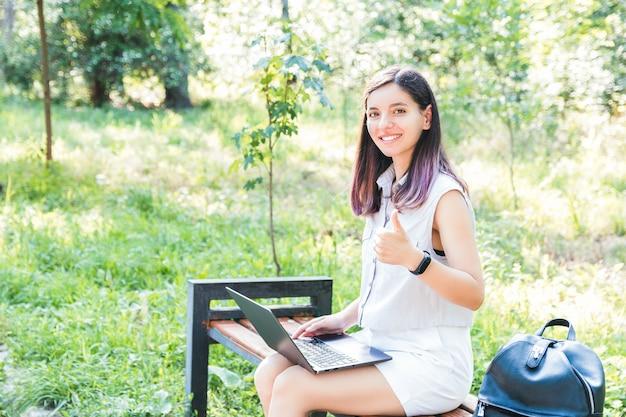 Wesoły młody student uczy się zdalnie na laptopie w parku, utrzymując dystans społeczny i ciesząc się samotnością
