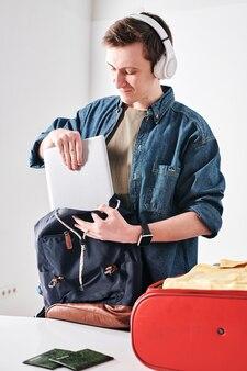 Wesoły młody student w słuchawkach bezprzewodowych pakujący tablet w tornister podczas podróży