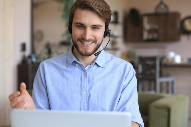 Wesoły młody wsparcie telefon mężczyzna operatora w zestawie słuchawkowym, w miejscu pracy podczas korzystania z laptopa, usługi pomocy i koncepcja call center konsultacji klienta.