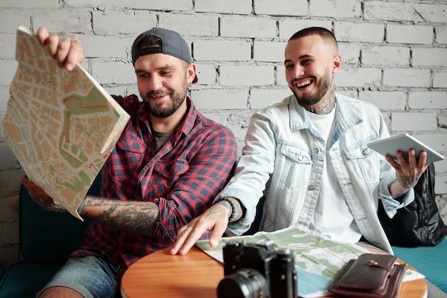 Wesoły młodzieniec przeglądający papierowe mapy i śmiejący się podczas omawiania trasy turystycznej