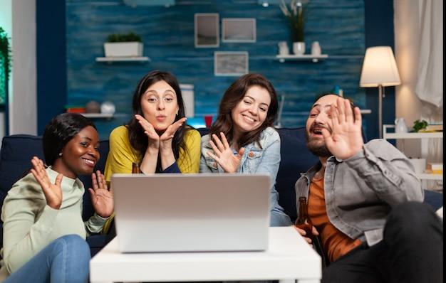 Wesoły multi etniczni przyjaciele machający do kamery podczas internetowej konferencji wideo online podczas zabawy. grupa wielorasowych ludzi spędzających razem czas siedząc na kanapie
