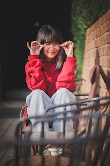 Wesoły nastolatek azjatyckich w okularach siedzi na biurko z drewna