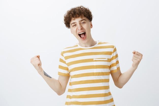 Wesoły nastolatek, pozowanie na białej ścianie