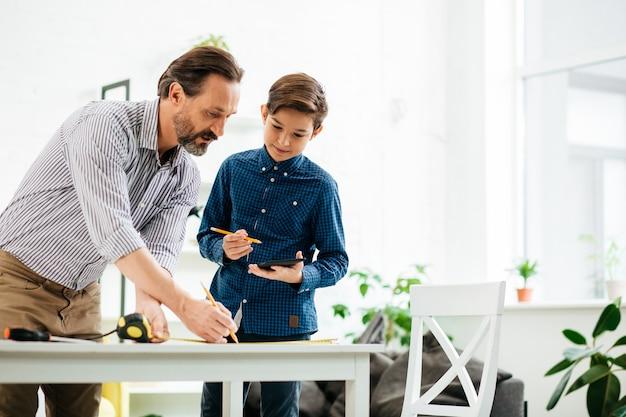 Wesoły nastolatek, uśmiechając się i patrząc na swojego brodatego ojca rysując linie na stole ołówkiem i centymetrem