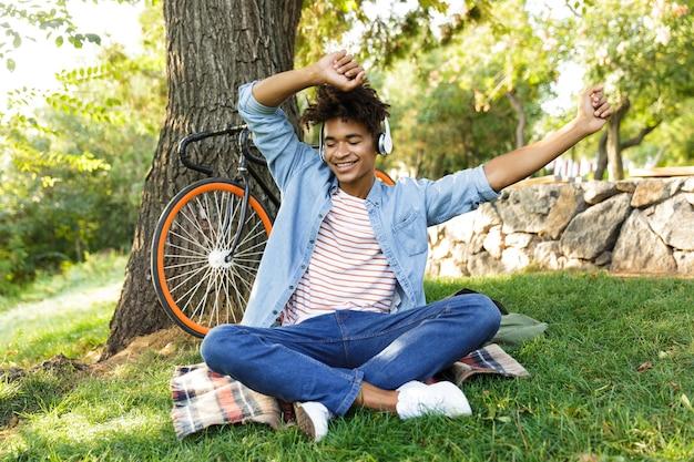 Wesoły nastolatek z rowerem na zewnątrz