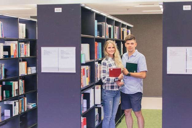 Wesoły nastolatków z książkami w bibliotece