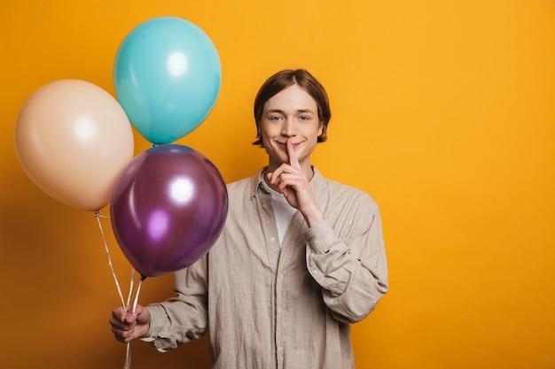 Wesoły nastoletni chłopak stojący w odosobnieniu, trzymający balony z powietrzem, pokazujący gest ciszy