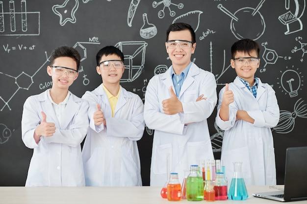 Wesoły nauczyciel przedmiotów ścisłych i grupa uczniów w fartuchach pokazujących kciuki do góry i patrząc