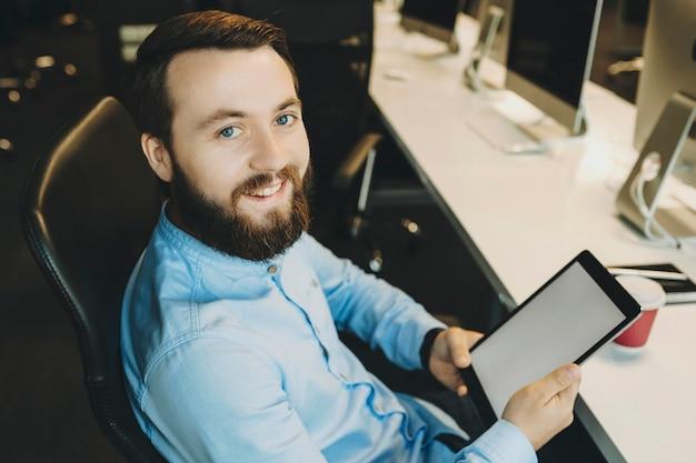 Wesoły nieogolony mężczyzna w niebieskiej koszuli siedzi wygodnie na krześle w miejscu pracy, trzymając w rękach tablet i uśmiechając się, patrząc na kamery