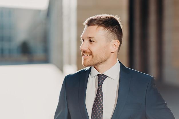 Wesoły, nieogolony mężczyzna wygląda z radosnym wyrazem twarzy, nosi formalne ubrania