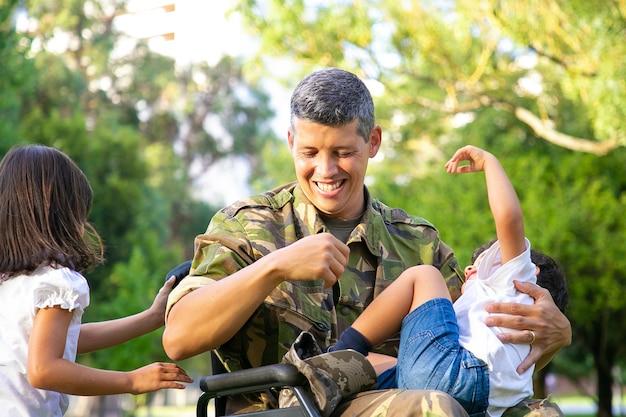 Wesoły niepełnosprawny tata wojskowy spędzający wolny czas z dwójką dzieci w parku. dziewczyna trzyma uchwyty na wózku inwalidzkim, chłopiec odpoczywa na kolanach ojców. weteran wojny lub koncepcji niepełnosprawności