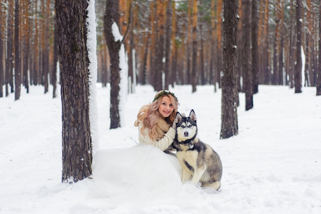 Wesoły nowożeńcy spacerują szlakiem w śnieżnym lesie z dwoma psami syberyjskimi.