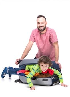 Wesoły ojciec i jego syn w walizce.