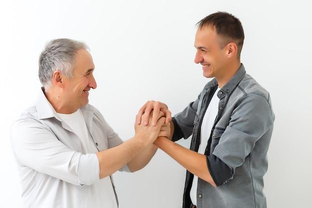Wesoły ojciec i syn przytulający się i pozujący razem na białym tle na białej ścianie