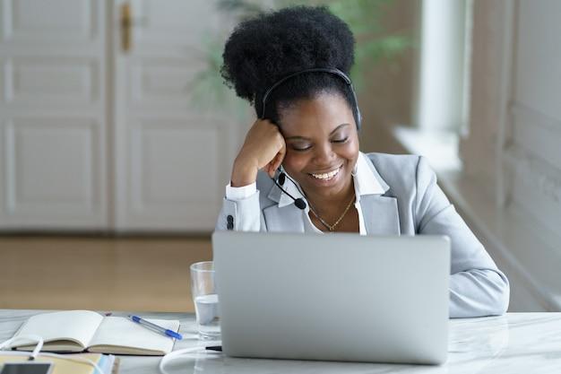 Wesoły operator obsługi klienta w słuchawkach przy laptopie komunikuje się z klientem podczas rozmowy wideo