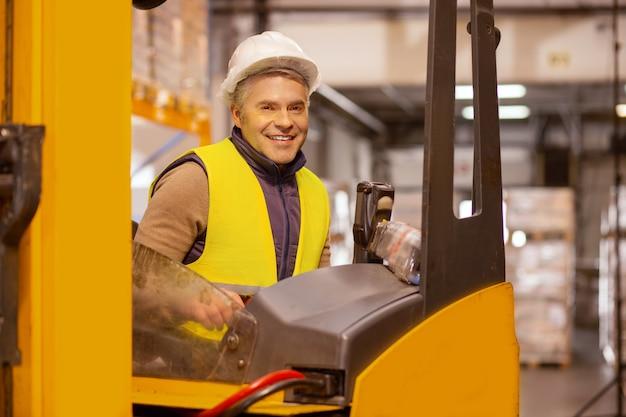 Wesoły operator pojazdu siedzący w specjalnym samochodzie podczas pracy w magazynie
