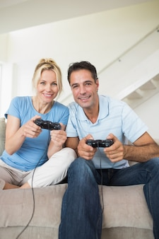 Wesoły para grając w gry wideo w salonie