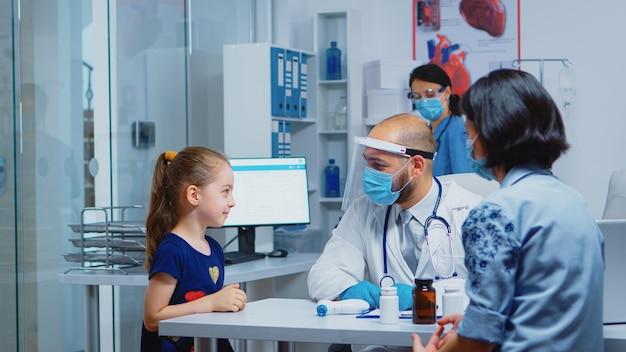 Wesoły pediatra uśmiechający się do małej dziewczynki podczas wizyty lekarskiej. specjalista medycyny w masce ochronnej udzielający świadczeń zdrowotnych, konsultacji, leczenia, badania w gabinecie szpitalnym.