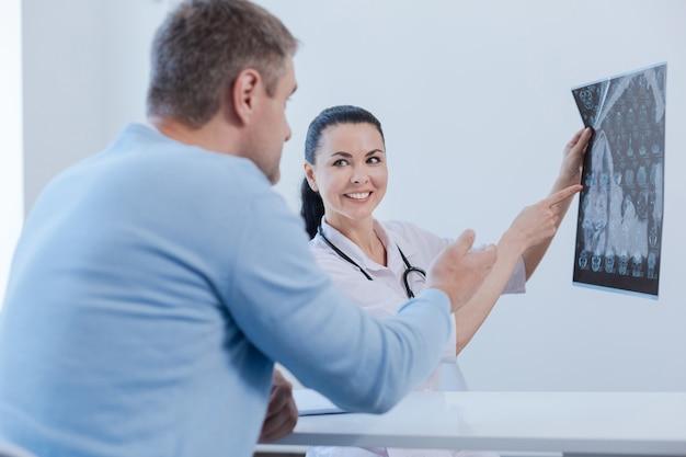 Wesoły, pewny siebie, doświadczony terapeuta cieszący się wizytą u pacjenta i analizujący badanie mr, wyjaśniając sposoby leczenia