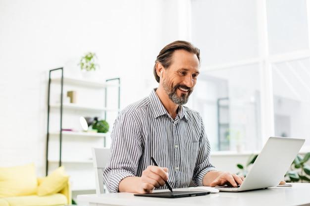 Wesoły pewny siebie mężczyzna w średnim wieku siedzący przy stole i patrząc na ekran swojego laptopa, trzymając rysik w prawej ręce